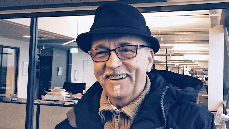 Vanhemnpi mies seisoo hattu päässä lähikuvassa.