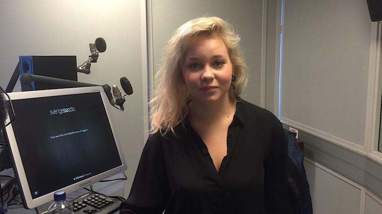 Vaaleahiuksinen Iris Sid seisoo studiossa musta paita päällään. Kuva/Bild: Timo Laine/SR Sisuradio