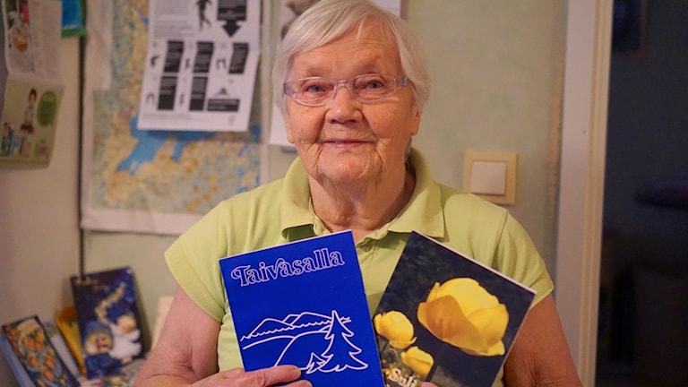 Kuvassa näkyy vanhempi naishenkilö joka katsoo kameraan, käsissään kaksi kirjaa.