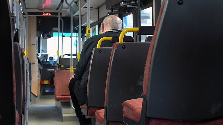 Kuvassa yksi mies istuu bussissa.