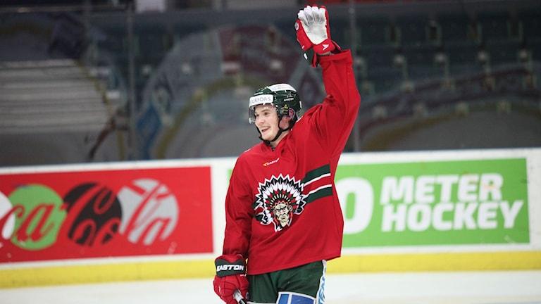 Iloinen jääkiekonpelaaja punaisessa pelipaidassa käsi ylhäällä