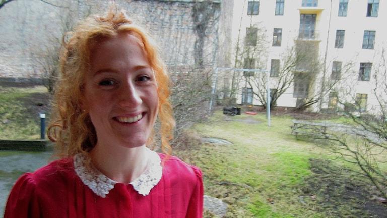 Ung rödhårig kvinna med röd blus.