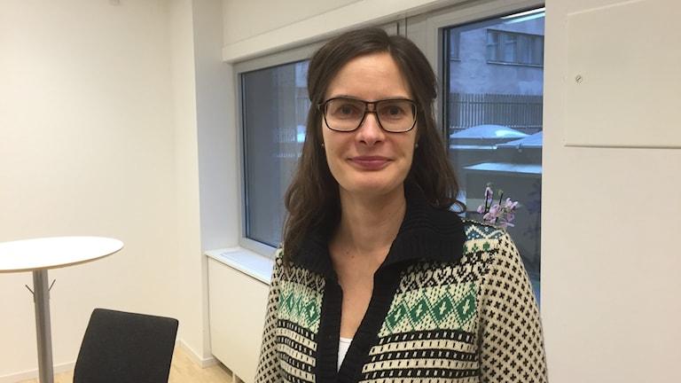 Johanna Raynal seisoo kirjavassa neuleessa toimiston neuvotteluhuoneessa. Kuva: Timo Laine/Sveriges Radio Sisuradio