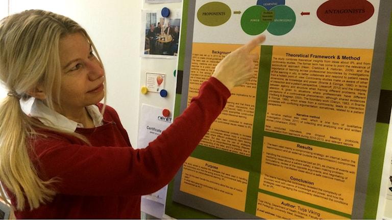 Tuija Viking näyttää sormella tutkimutuloksistaan kertovaa taulua. Kuva:Ulla Rajakisto/Sveriges Radio Sisuradio