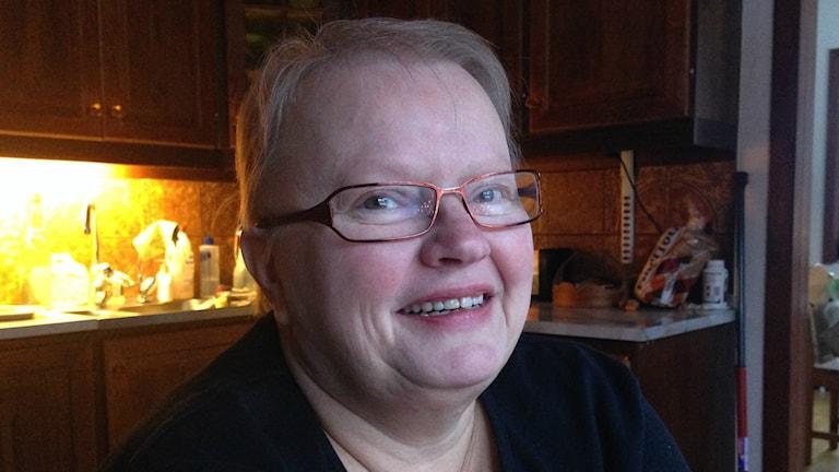 Silmälasipäinen Tuula Halonen Brännlund istuu keittiössä, jossa on tumman ruskea kaapisto. Kuva/foto: Erpo Heinolainen SR Sisuradio