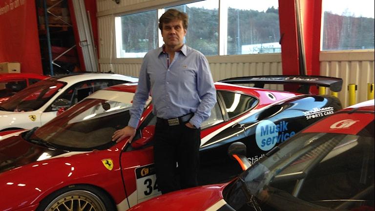 Vaaleansiniseen kauluspaitaan ja mustiin housuihin pukeutunut Kari Mäkinen seisoo kilpa-autojen keskellä. Kuva/foto: Erpo Heinolainen SR Sisuradio