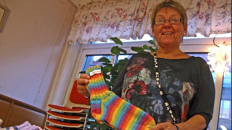 Vanhempi nainen lähikuvassa pitää sukkaparia kädessään joulumyyjäisissä.