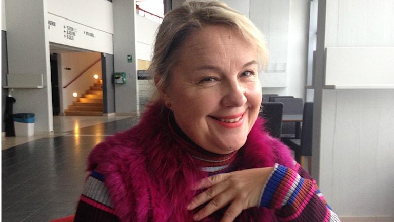 Anu Komsi violetin sävyisissä vaatteissaan hymyilee, taustallaan Norlannin oopperan aula. kuva/foto. Erpo heinolainen SR Sisuradio