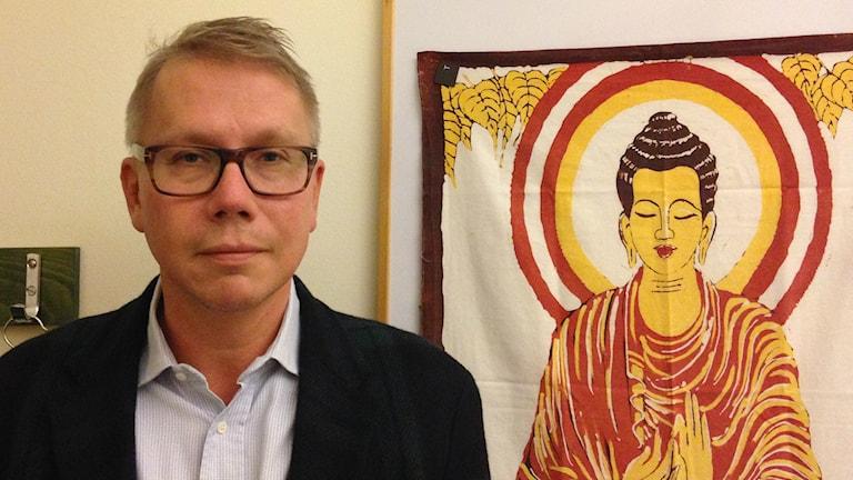 Silmälasipäinen Jussi Jokinen, tummassa pikkutakissaan seisoo budhalaiskuvan vieressä. Kuva/foto: Erpo Heinolainen SR Sisuardio