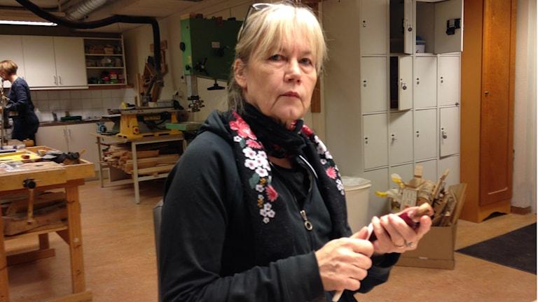 Arja Fox seisoo työpajassa puukko kotelossa ja hioo koteloa. Kuva/foto: Erpo Heinolainen SR Sisuradio