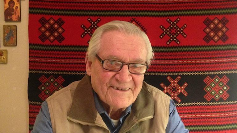 Harry Permanto hymyilee taustanaan karjalaisryijy ja ikoneita. Kuva/foto: Erpo Heinolainen SR Sisuradio