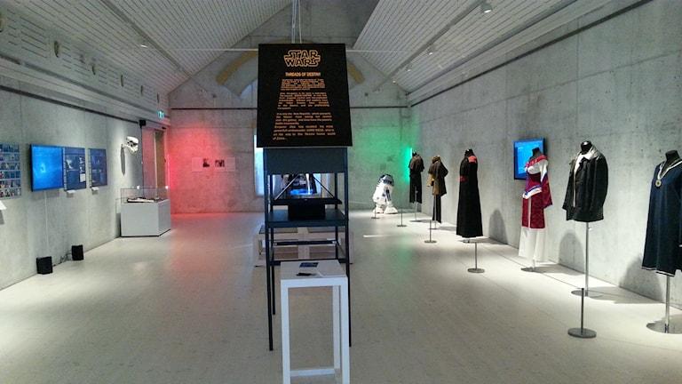 Tähtien sota-näyttelyyn kuuluu paljon rekvisiittaa, kuva näyttelyn ovelta. Vasemmalla video, joka näyttää miten erikoisefektit toimivat, oikealla video kenraaliharjoituksista. Kuva Pekka Ranta, Sveriges Radio.