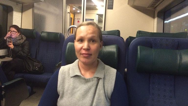 Eva Joensuu istuu junassa ja katsoo kameraan