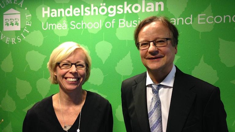 Vaaleatukkainen Sofia Lundberg ja tummatukkainen Jorma Larimo hymyilevät leveästi Uumajan kauppakorkeakoulun vihreän seinän edessä. Kuva/foto: Erpo Heinolainen SR Sisuradio