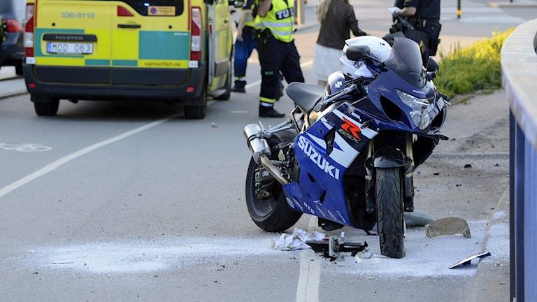 Vioittunut moottoripyörä tien laidassa onnettomuuden jälkeen. Taustalla ambulanssi. Foto: Bertil Enevåg Ericson / TT
