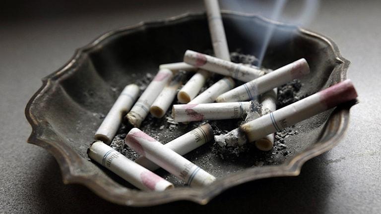 Tuhkakupissa käryäviä tupakantumppeja. Foto: Dave Martin / AP.