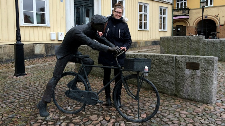 Mariestadin hallintoaluekoordinaattori Carolina Nordling seisoo pyöräilijäpatsaan vierellä Mariestadin keskustassa