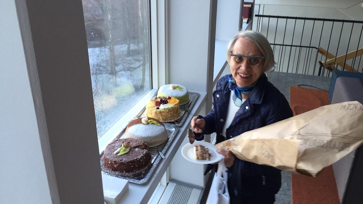 Kaarina Wallin hymyilee kukkakimppu kädessään kakkujen edessä. Kuva: Marika Pietilä / Sveriges Radio Sisuradio