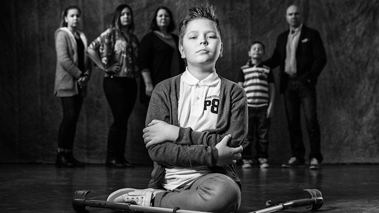 Taistelutarinat-sarjan mustavalkoinen kuva, jossa lapsi Oskari istuu lattialla kädet puuskassa, leuka pystyssä ja viisihenkinen perhe taustalla. Kuvaaja: Lari Järnefelt