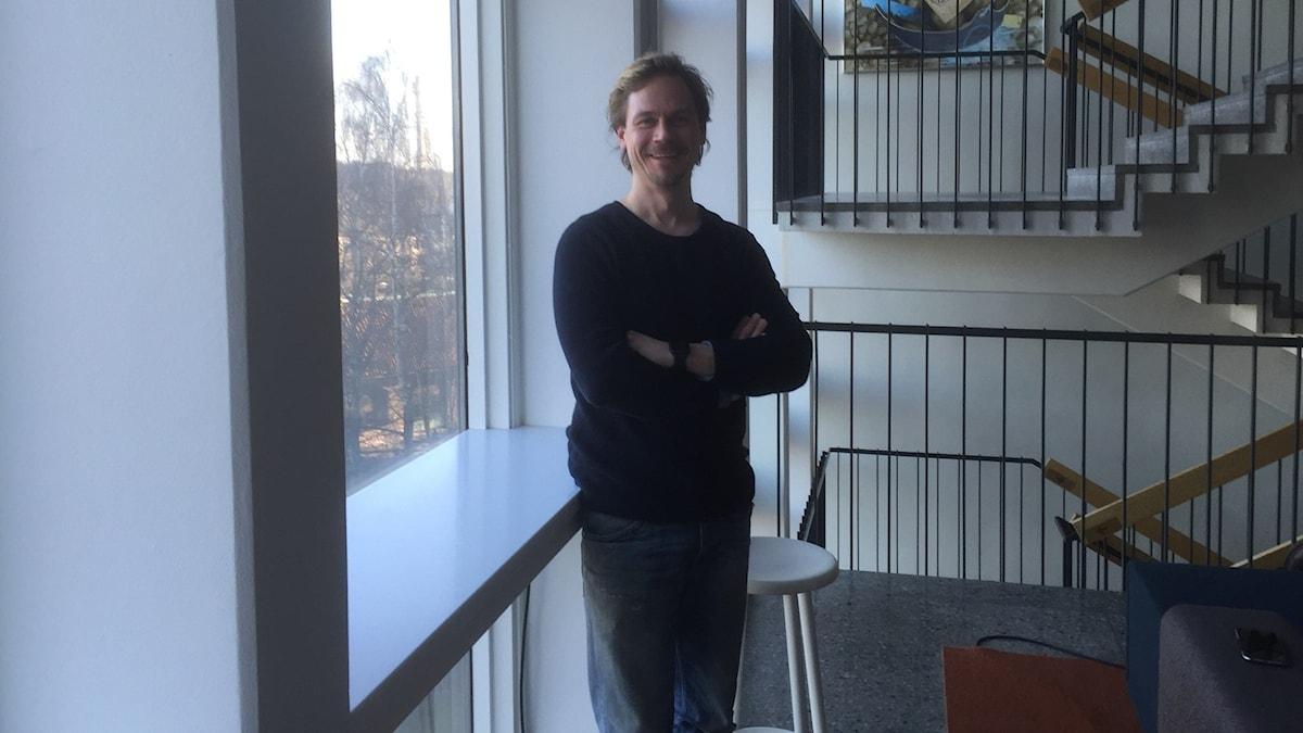 Lari Järnefelt seisoo ikkunan vieressä katsoen hymyillen kameraan, taustalla portaikko. Kuvaaja/Fotograf: Timo Laine/Sveriges Radio Sisuradio