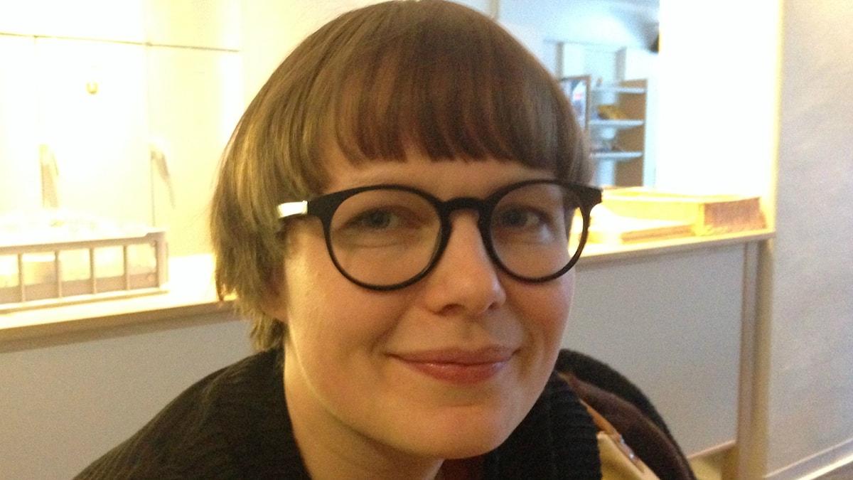 Pyöreäsilmälasinen Hanna Kangassalo katsoo suoraan kameraan. Vaaleassa taustassa kahvikuppitelineitä.