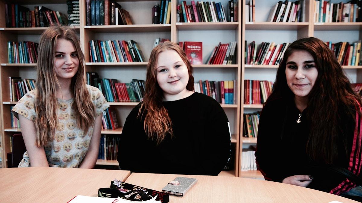 Viivi Paavonperä,Jaana Salo ja Denise Kayani istuvat kirjahyllyn edessä koulun kirjastossa.