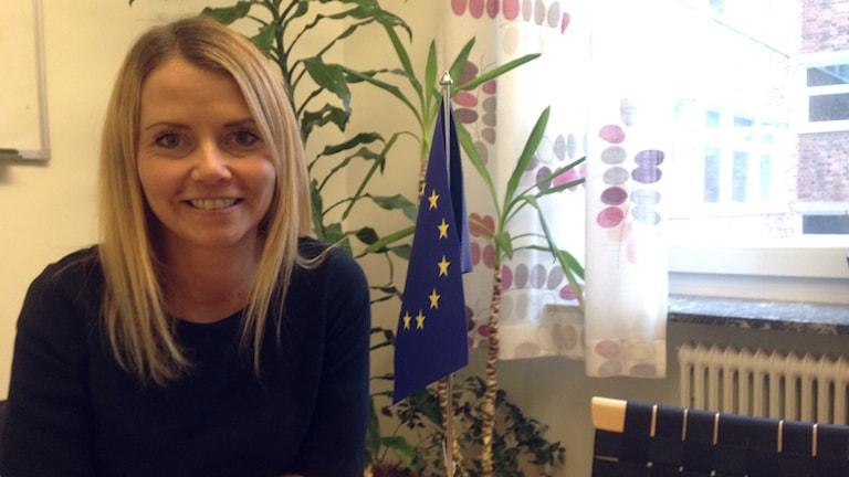 Linda Harju hymyilee EU lipun vieressä.