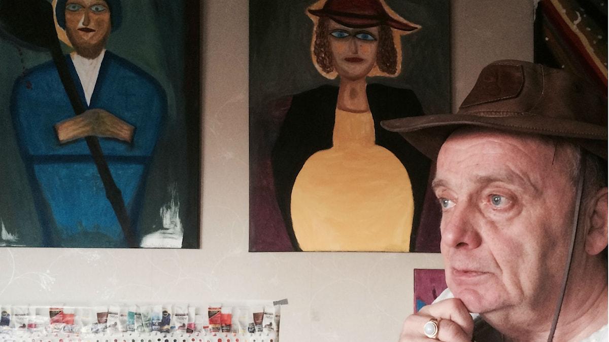 Arvo Paananen mietiskelee maalaustensa vieressä, toisessa sininen pyöveli ja toisessa keltamekkoinen raskaana oleva nainen