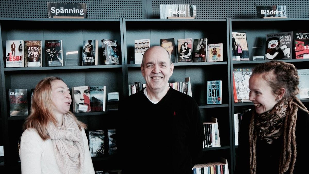 Lukupiiriläiset Anna Pilvinen, Keijo Knutas ja Hanna Hallakumpu naureskelevat kirjastohyllyn edessä. Foto: Kai Rauhansalo