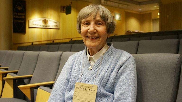 En äldre kvinna med en ljusblå tröja sitter och ler.