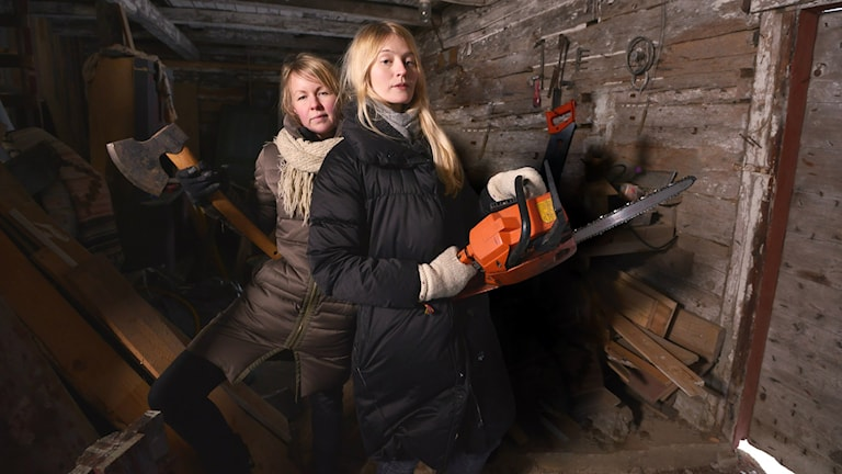 Lina Puranen kirves kädessään ja Maija Waris moottorisaha kädessään puuvajassa.