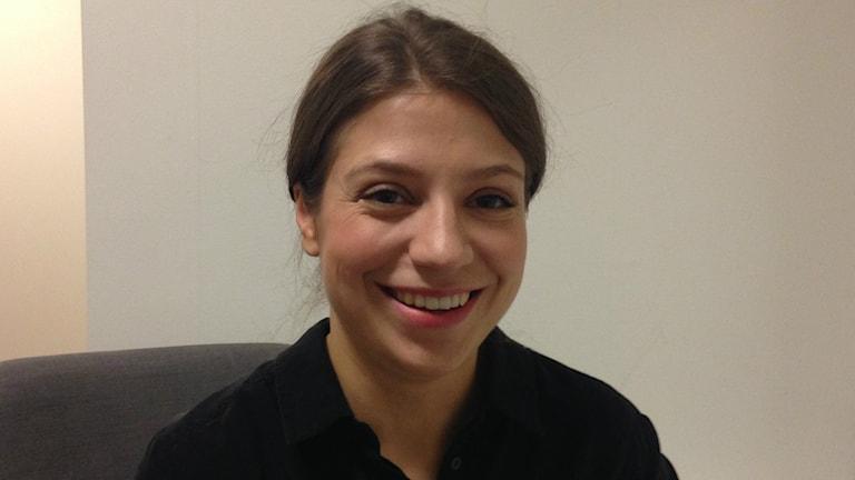 Tummatukkainen ja mustapuseroinen Dalia Stasevska hymyilee taustanaan vaalea seinä.