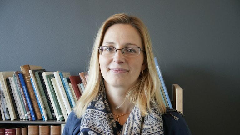 Maria Balaban, en blond kvinna med glasögon tittar mot kameran och ler