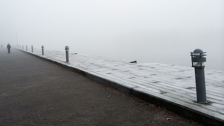 Sumuinen laituri meren äärellä Göteborgissa, missä kävelee yksi ihminen.
