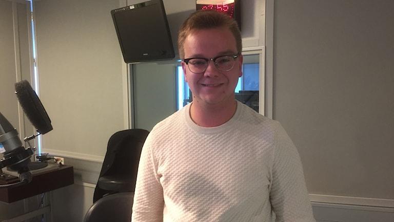 Mika Metso seisoo hymyillen vaalea paita päällään. Kuva/Foto: Timo Laine/Sveriges Radio Sisuradio