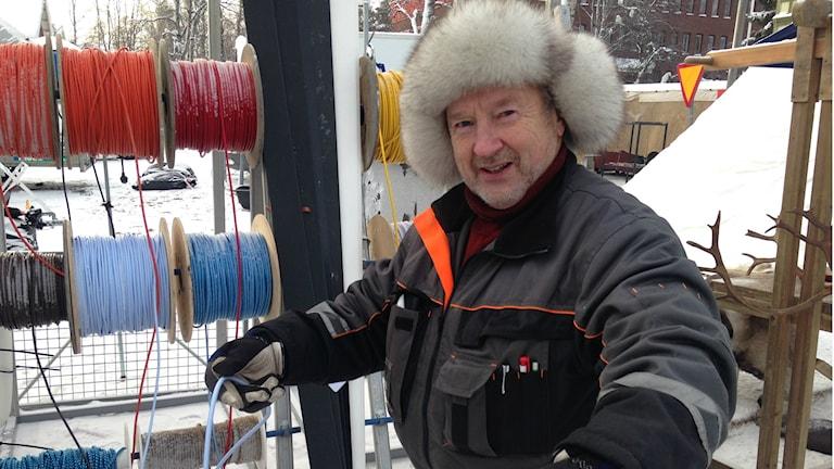 Hannu Nurmi mittaa sylimitalla vaaleansinistä suopunkiköyttä. Rullissa runsaasti muitakin värejä.