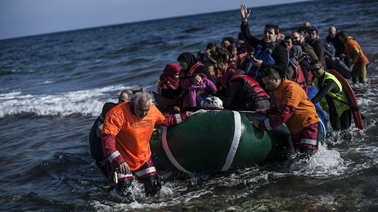 Kuvassa näkyy aalloilla keikkuva kumivene täynnä ihmisiä.