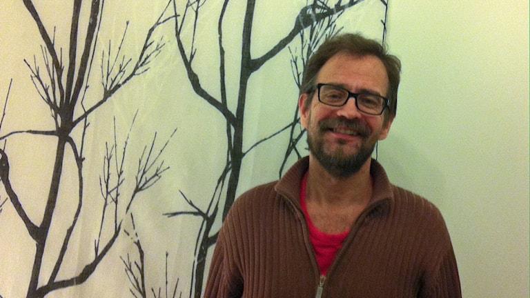 Jussi Sorell står framför ett konstverk med trädsiluetter på en vägg.
