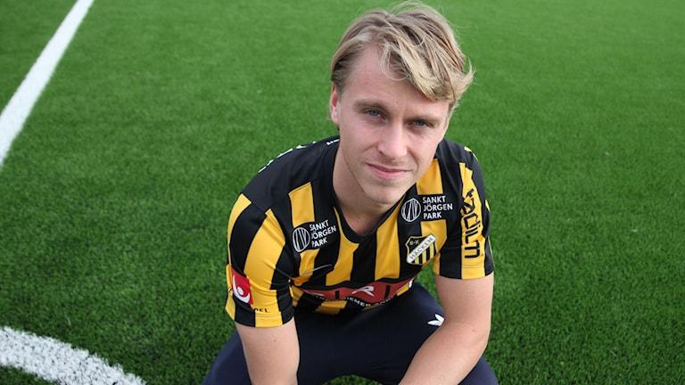 Kuvassa kameraan katsova, vaaleahiuksinen mies joka istuu jalkapallokentällä peliasu päällään.