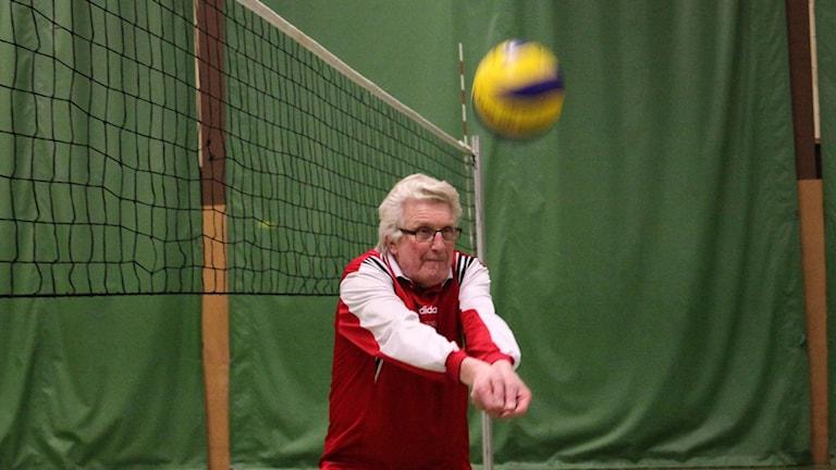 Kuvassa näkyy harmaahiuksinen mies joka pelaa lentopalloa.