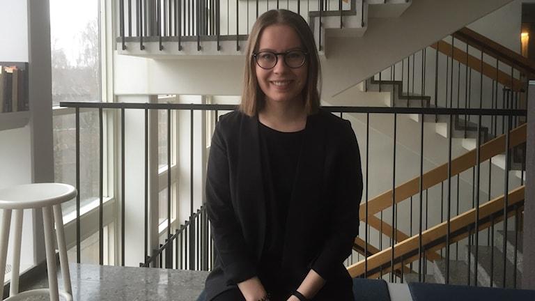 Silmälasipäinen Karoliina Möttönen istuu kädet sylissä katsoen hymyillen kameraan. Kuva: Timo Laine/Sveriges Radio Sisuradio