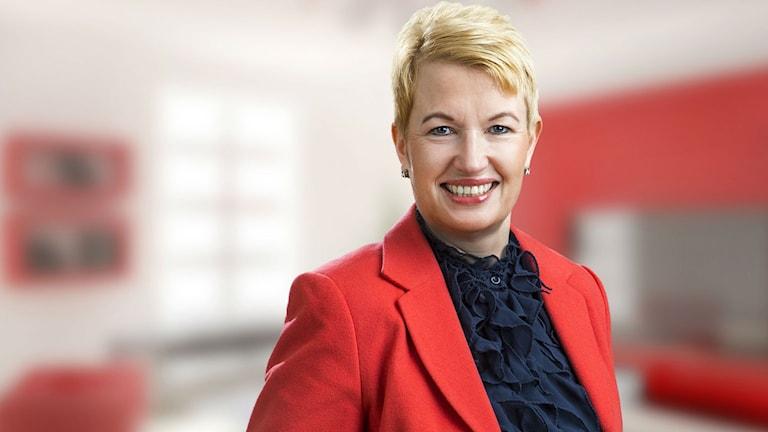 Punaiseen takkiin pukeutunut Nina Jönsson hymyilee ja katsoo kameraan. Foto: ICA