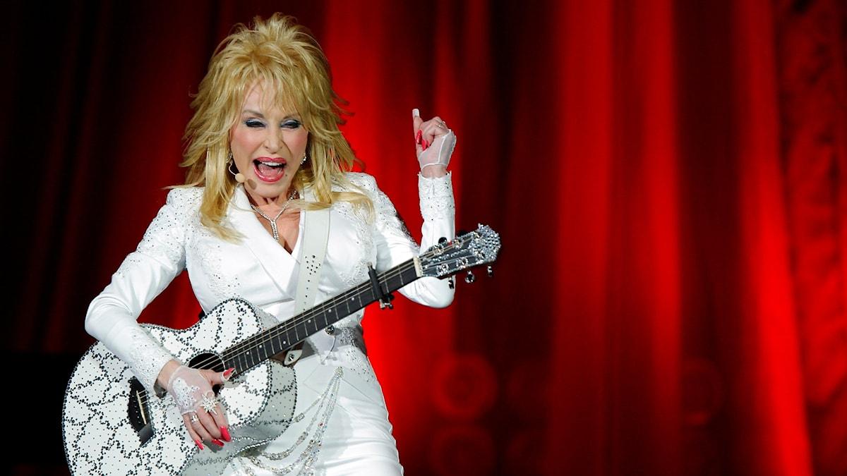 Dolly Parton valkoisissa vaatteissa valkoinen kitara kädessään punaista taustaa vasten.