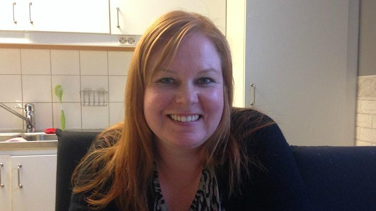 Mari Destin katsoo kameraan ja hymyilee, hänellä on punertavat hiukset ja taustalla keittiön kaappeja.