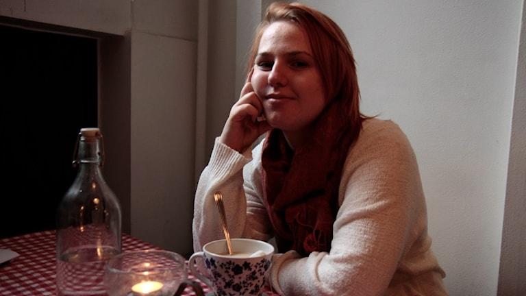 Anna-Josefiina Turtiainen istuu kahvilassa mietiskelevä ilme kasvoillaan. Foto: Kai Rauhansalo
