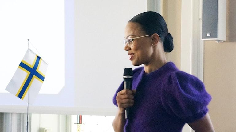 Sverigefinnarnas flagga och kulturminster Alice BAh Kuhnke i en lila tröja