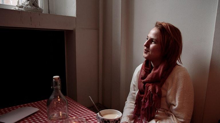 Anna-Josefiina Turtiainen istuu kahvilassa ja katsoo ulos ikkunasta. Foto: Kai Rauhansalo