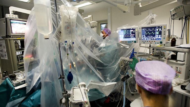 Etulalalla hoitaja ja takana leikkaupoöydällä oleva potilas, joka on lähes kokonaan erilaisten muodien ja sairaalalaitteiden peitossa. Kaiken takana näkyy monitoreissa erilaisia käyriä. Kuvassa on käynnissä eturauhaspotilaan tähystysleikkaus.