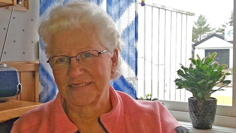 Erja Ahlqvist on puuhanainen, joka on mukana järjestämässä Gislavedin Suomiseuran 50-vuotisjuhlaa. Hänellä on valkea tukka, silmälasit ja vaaleanpunainen jakku.