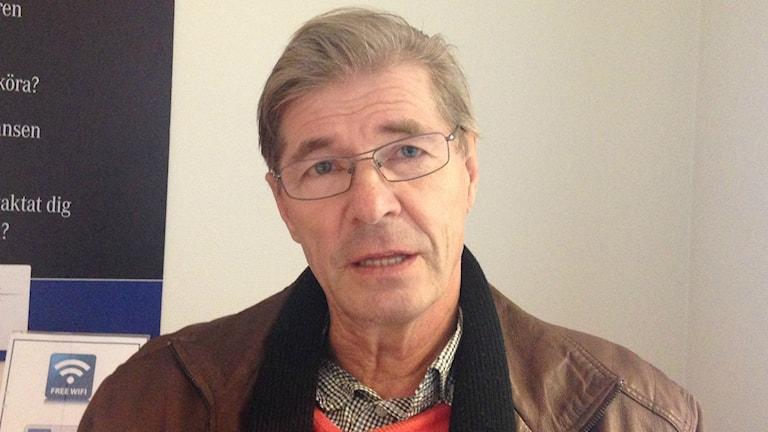 Silmälasipäisellä Matti Heikkisellä on yllään ruskea nahkatakki, jonka alla oranssi neule ja pieniruutuinen kauluspaita.